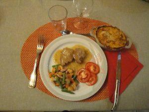 Un plat appétissant avec viande en sauce, jardinières de légumes, rondelle de tomates et gratin.