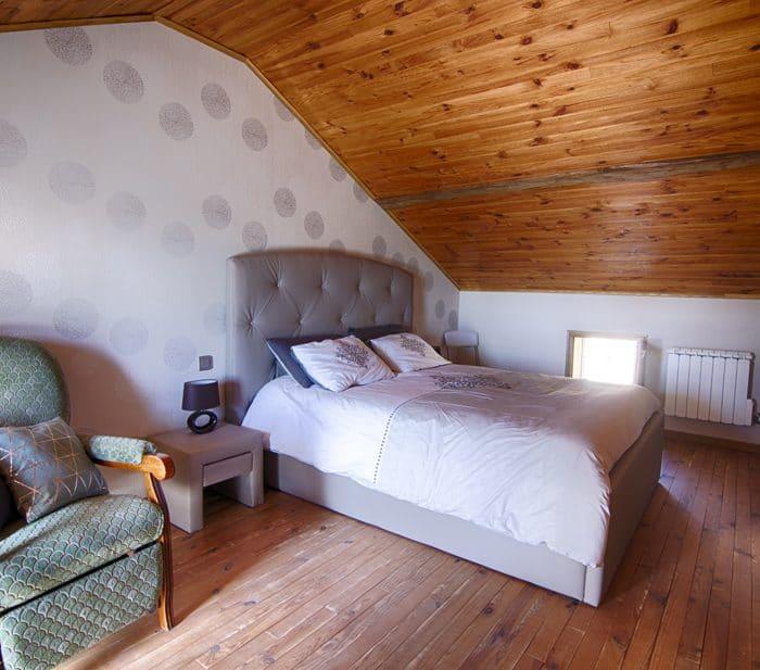 Le fauteuil et le lit de la chambre double.