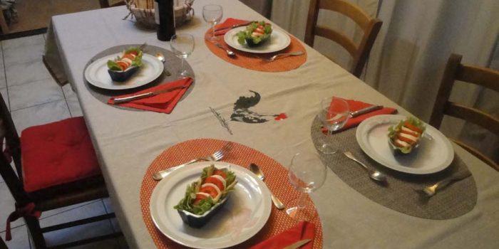 La table du repas avec assiettes, couverts, entrée, vin et corbeille à pain.